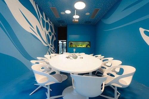 Stanza uffici microsoft con tavolo e sedie bianche e pareti blu