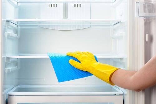 mano che pulisce l'interno di un frigorifero