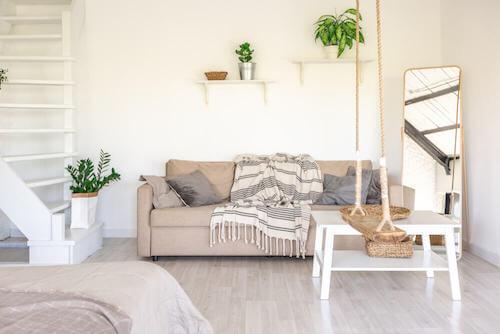 soggiorno con divano e piante in stile urbano funzionale