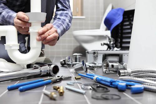 Idraulico che ripara le tubazioni in bagno