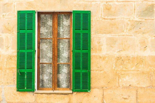 persiane aperte su facciata in pietra