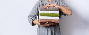 Uomo sorregge degli asciugamani ordinati