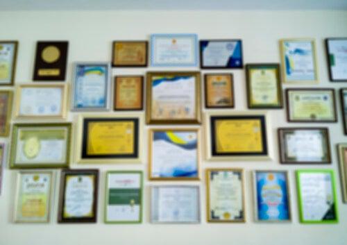 Lauree e altri titoli alle pareti dell'ufficio.