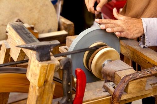 artigiano che affila un coltello con un'affilatrice antica