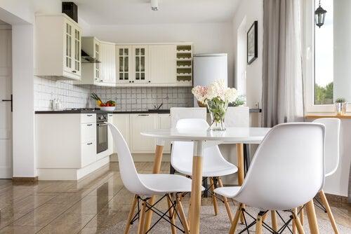 Decorare appartamento per studenti. Cucina bianca con pavimento in pseudo legno.