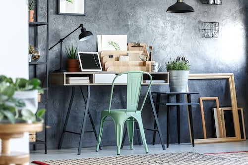 tavolo scrivania con piante sedia in ferro e parete grigia