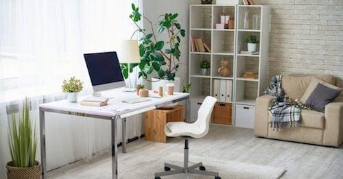 tavolo e sedia bianchi con libreria e divano e piante