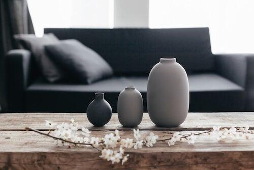 vasi tonalità grigio su tavolo in legno con ramo di ciliegio in fiore