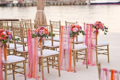 sedie bianche con decori color salmone per un matrimonio