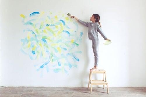 Bambina che dipinge una parete.
