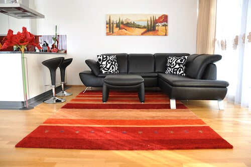 Salotto con divano in pelle nera e tappeto colore arancione rosso.