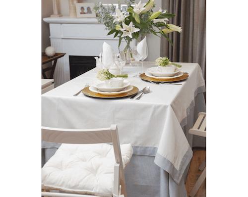 tavoli modello camilla tavolo apparecchiato con tovaglia bianca e azzurro e centrotavola con fiori