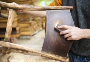 Uomo usa tecnica decapaggio su sedia in legno