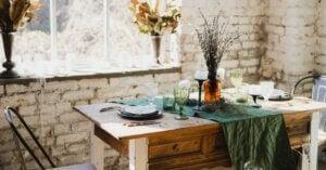 Tavolo in stile rustico apparecchiato con piatti e bicchieri e un vaso