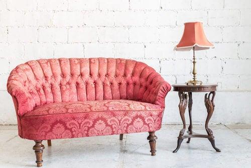 divano rosa con schienale trapuntato tavolino con lampada