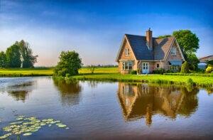 Esempio di cottage inglese che si riflette su specchio d'acqua
