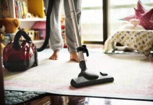 Donna passa l'aspirapolvere per mantenere la casa in ordine