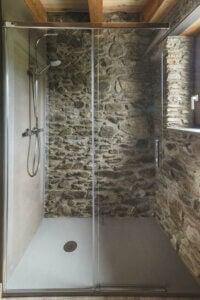 Doccia con pareti in pietra e soffitto in legno