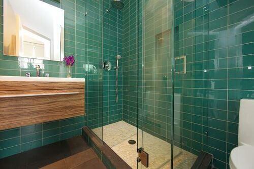 Colori forti: bagno verde smeraldo con lavandino in legno