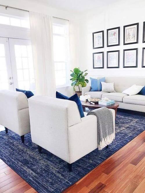 Salotto con tappeto cuscini blu divano poltrone e tende bianche