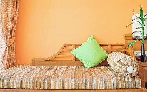 Divano letto con parete arancione.