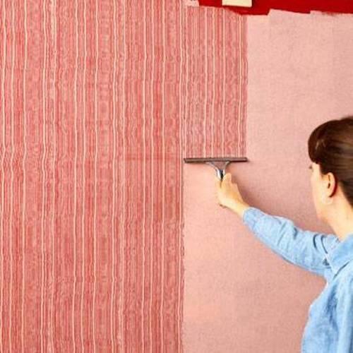 Donna stende la pittura decorativa effetto pettinato.