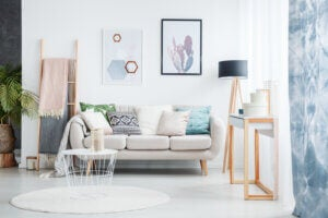 Trucchi per rendere più luminoso un salone piccolo: divano con cuscini e coperte