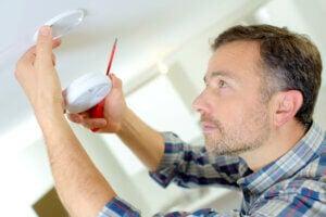 Uomo installa sistema antincendio in casa