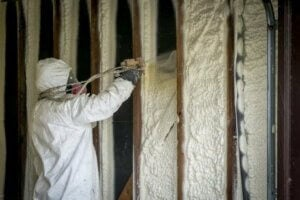 Uomo installa impianto di isolamento termico.