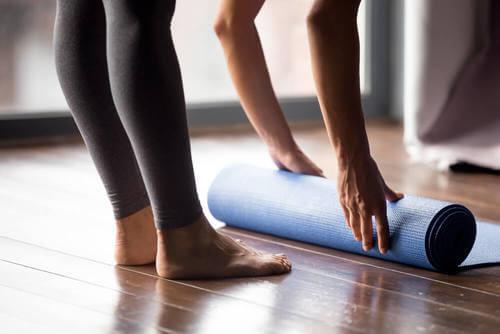 Donna che avvolge un tappetino per lo yoga.