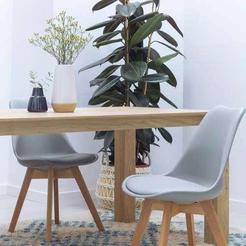 Mobile in legno chiaro con pianta e sedie grigie.