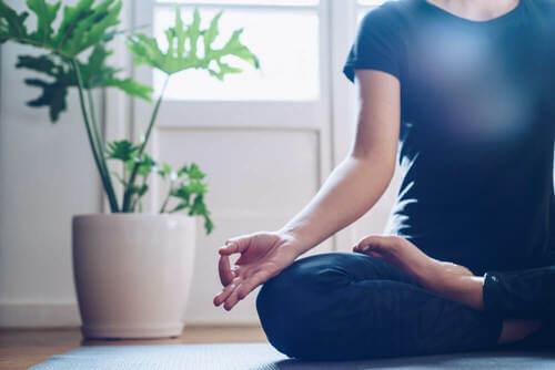 Donna che fa yoga seduta sul pavimento.