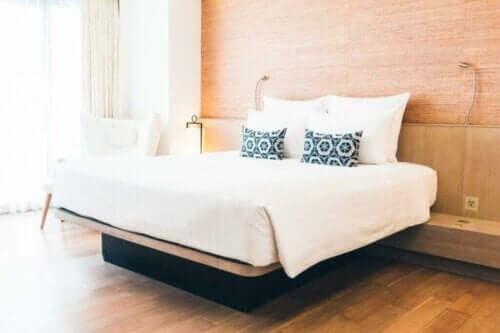 Come la casa influenza il benessere psicologico. Camera da letto con parete in legno e parquet.
