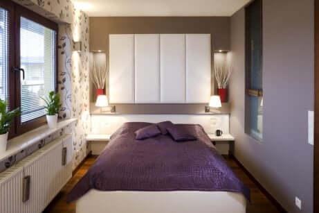Camera da letto piccola con testiera bianca.