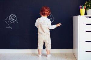 Bambino che disegna su una parete.
