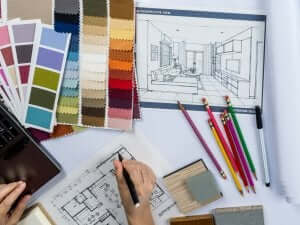 Un designer d'interni lavora a un progetto con delle palette di colori.