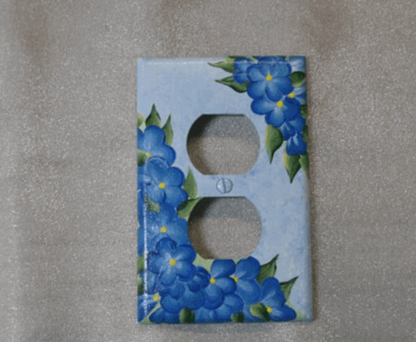 Copri presa elettrica dipinto con dei fiorellini.