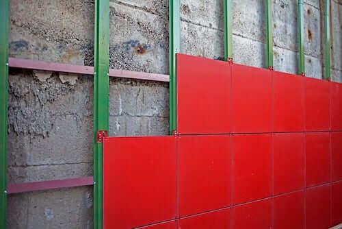 Facciate ventilate. Facciata ventilata con pannelli rossi installata su muro di cemento.