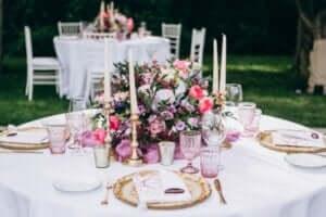Una tavola romantica con fiori e bicchieri rosa.