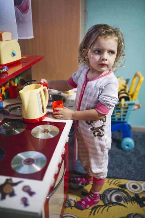 Bambina che gioca con una cucina giocattolo.