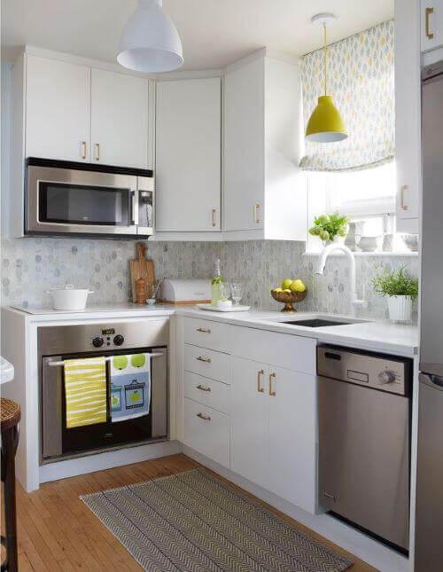 Cucina piccola con mobili bianchi.
