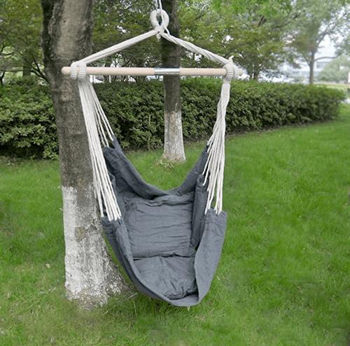 Poltrona sospesa appesa su un albero in giardino.