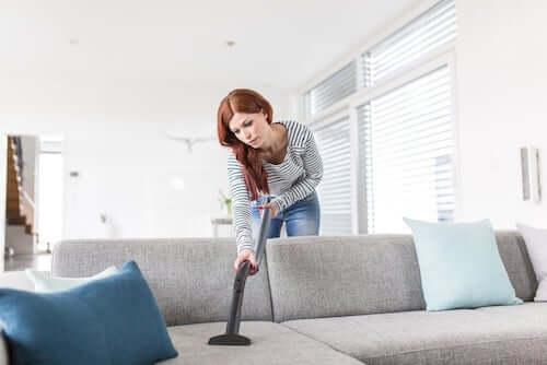Donna che pulisce il divano con l'aspirapolvere.