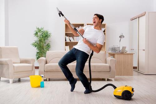 Uomo che si diverte mentre pulisce il salotto con l'aspirapolvere.