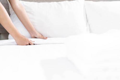 Donna che rifà il letto.