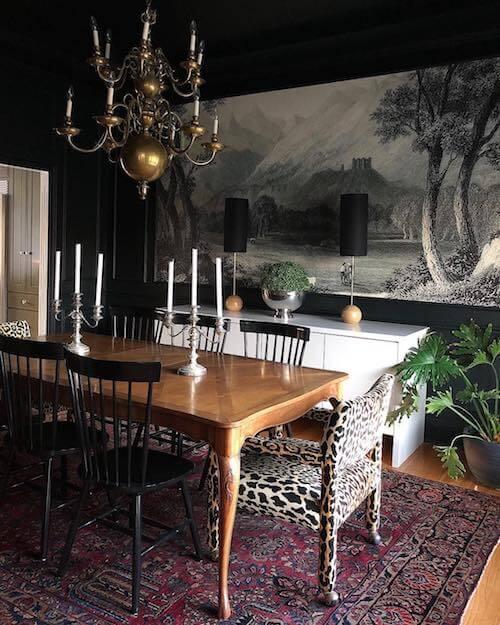 Sala da pranzo elegante con tappeto persiano, lampadario dorato e poltrone con stampe animalier.