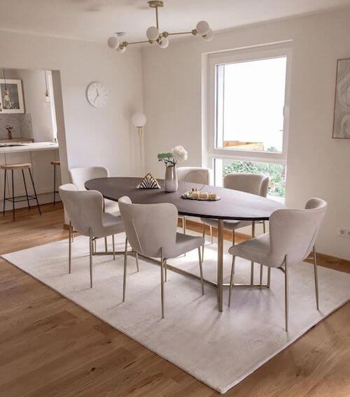 Tavolo ovale e sedie bianche con elementi dorati.