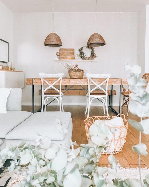 Tavolo in legno massello, sedie bianche e lampade in fibra naturale.