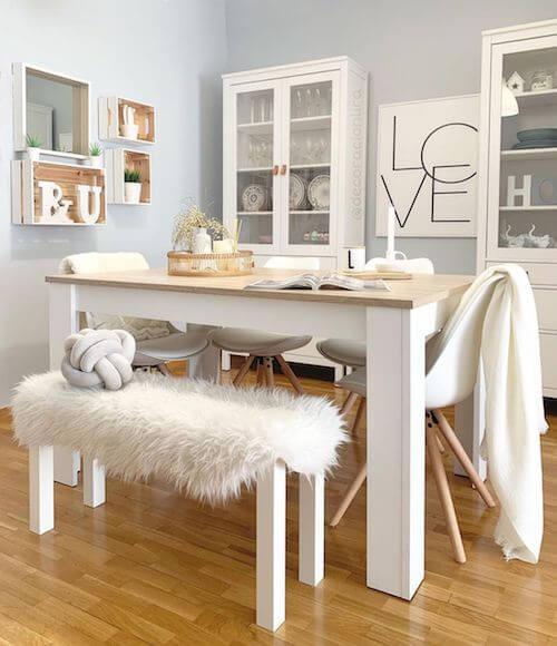 Sala da pranzo con tavolo e sedie in legno bianco.