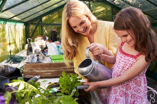 Madre e figlia che annaffiano una pianta.